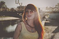 Head and shoulders of ginger hair woman in orange color sunglasses backlit vintage color grading