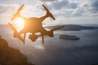 Unmanned Aircraft System (UAV) Quadcopter Drone In The Air At Sunset Over The Greek Isles.