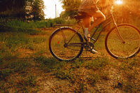 Vintage image of young hipster female on city bike fixie at the park. Summertime. Freedom teenager with her happy vacation travel retro look