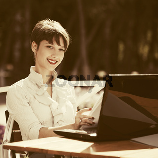 Young fashion business woman using laptop at sidewalk cafe