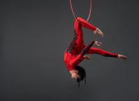 Young slim gymnast with red hoop studio portrait
