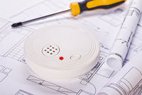 Smoke detector with blueprints and screwdriver