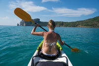Woman kayaking in turquoise sea during summer day