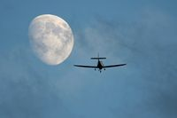 light aircraft flying towards the moon