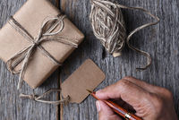 Closeup of a plain wrapped Christmas gift with a man ready to fill out the blank tag.