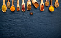 Various of Indian spices and herbs in wooden spoons. Flat lay of spices ingredients chilli ,pepper, garlic,dries thyme, cinnamon,star anise, nutmeg,rosemary, sweet basil and kaffir lime on dark stone.