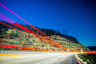 semi and car trails on highway drving through mountains at night