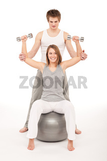 Young couple with weights and fitness ball on white