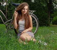 Beautiful smiling girl sitting next to bike on fresh grass with her eyes half closed