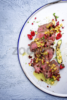 Australian barbecue dry aged Kobe chateaubriand steak with vegetable and fruit relish as close-up on a white plate