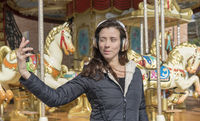 happy, woman next to a merry-go-round taking selfie with the cell phone on a spring afternoon. image of freshness and lifestyle in europe