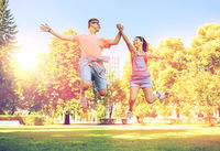 happy teenage couple jumping at summer park