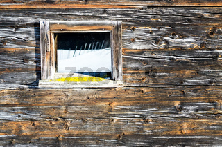 Vintage window of old wooden cabin mirrors winter landscape. Wooden rustic background.