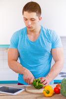 Junger Mann kochen Essen Gemüse Mittagessen Internet Tablet Hochformat gesunde Ernährung
