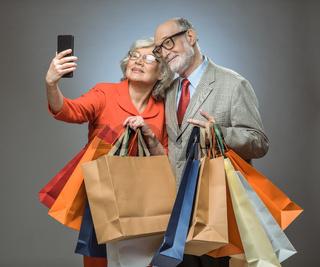 Senior couple taking selfie after shopping