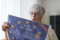 An elderly lady reading the news from the Proposed referendum on United Kingdom membership of the Eu