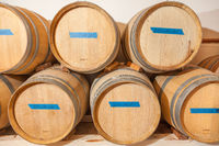 Wine Barrels and Bottles Age Inside Dark Cellar.