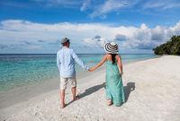 Vacation Couple walking on tropical beach Maldives.