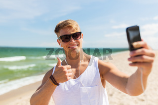 man with smartphone taking selfie on summer beach