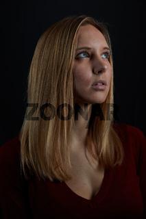 Junge blonde Frau schaut hoffnungsvoll nach oben
