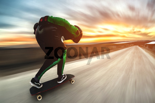 A man in a helmet and leather suit, in a rack at high speed, rides on a long longboard for downhill on afsalt against the backdrop of the setting sun in the light of the setting sun.