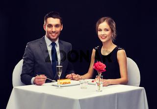 smiling couple eating dessert at restaurant