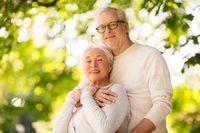 happy senior couple hugging at summer park