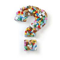Question mark from red pills and capsules on white background. Medical and drug issues concept.