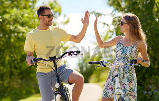 happy couple with bicycles making high five