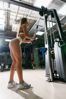 Young sexy fitness trainer exercising in gym