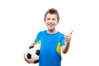 Handsome smiling child boy holding soccer ball gesturing thumb up success sign