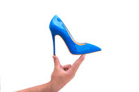 Blue lacquered female shoes in a male hand on a white background