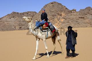 Tuareg Führer mit Tourist auf einem Reitkamel während einer Exkursion im Akakus-Gebirge Libyen / Tuareg guide with tourist riding on a dromedary during an excursion in the Acacus Mountains