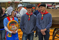 Dutch cheese girl with a Gouda cheese truckle and two cheese boys, cheese market Gouda, Netherlands