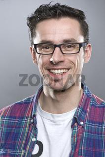 Junger dunkelhaariger Mann mit Brille lächelt