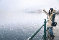 Woman reaching snowflakes on a snowy day