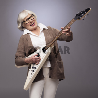 Senior woman playing electric guitar