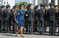 Woman in military uniform striding past a group of male members of the Mongolian armee at a parade