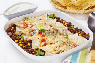 Mexican beef and sweetcorn enchiladas with sour cream and corn chips.