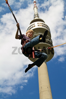 Fliegender Junge vor Münchner Olympiaturm