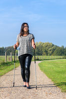 Young woman hikes with Nordic Walking sticks