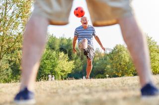 Aktiver Senior beim Fußball im Park