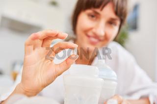 Mutter mit Vitamintablette und Babynahrung
