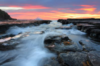 Sunrise waves flowing into rock chasm seascape
