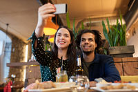happy couple taking selfie at cafe or bar