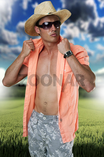 Portrait of attractive man standing with shirt unbuttoned wearing sunglasses on green field bacground