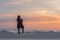 Girl in a fur coat against the background of a winter evening sky