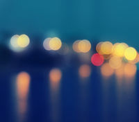 Square image of a blurred city lights with bokeh effect reflected on water.