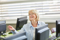 Glückliche ältere Frau im Computerkurs