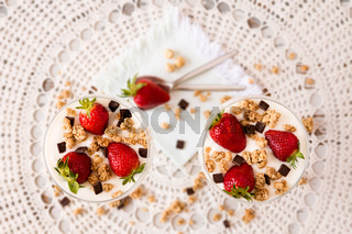 Strawberries cereals and chocolate flakes in two cups of plain yogurt